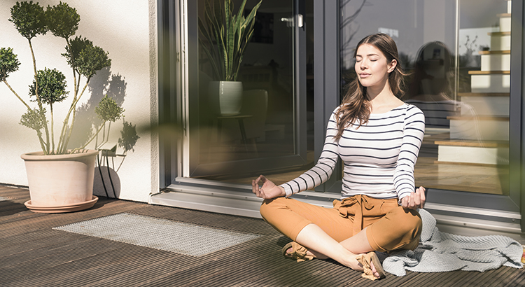 Woman meditating outside in sunshine