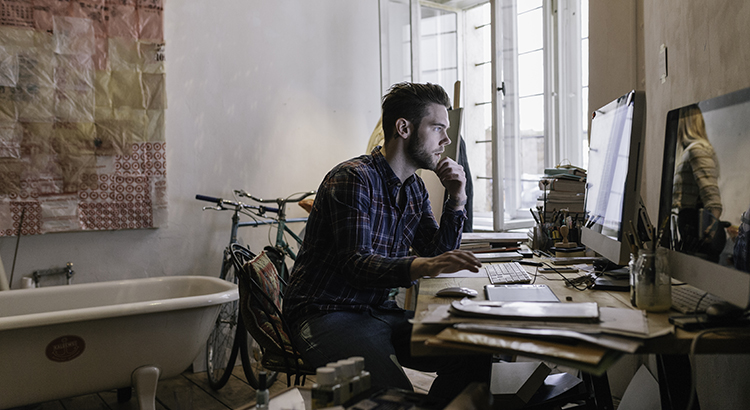Young creative man working in his home office. He is looking at computer screen